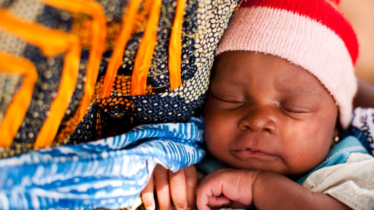 A child sleeps in her mother's arms after getting vaccinated in the village of Banankoro, Mali on Saturday August 28, 2010.