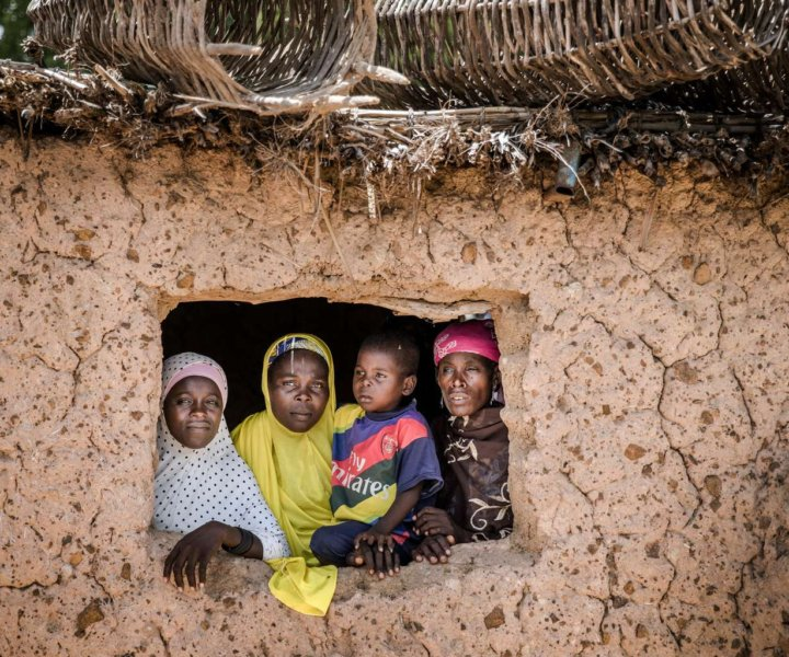 Several member of a family look from the windows of their house upon the arrival of a United Nations convoy in the village of Dargué, Maradi region, Niger on August 16, 2018. Several UN Agencies (FAO, WFP and IFAP) along with the Government of Niger and other partners visited the agropastoral Maradi region of Niger to understand  the context and local priorities, especially the needs of women and other vulnerable groups in the area. In Niger, as in many other parts of the Sahel, climate shocks have resulted in recurring droughts with devastating impacts on the region's already vulnerable populations. / AFP PHOTO / Luis TATO