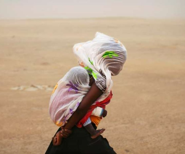 A woman carrying her baby and wrapped with a shawl walks through a sandstorm in Timbuktu July 29, 2013.  REUTERS/Joe Penney (MALI - Tags: SOCIETY ENVIRONMENT TPX IMAGES OF THE DAY) FOR BEST QUALITY IMAGE ALSO SEE: GM1E9AB18FD01 - GM1E97U0Q0T01
