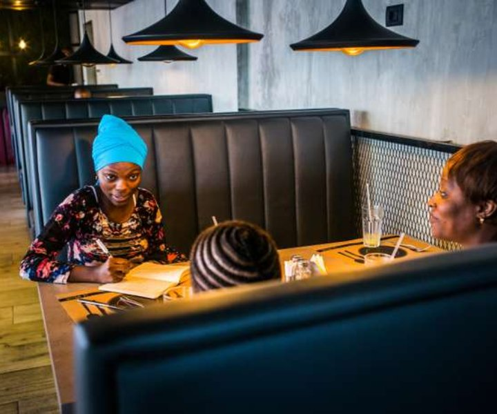 13 December 2017. Conakry, Guinea. Hadja Idrissa Bah discusses with a young adolescent and her mother who contacted her to get help, in a café in Conakry. The young girl was raped a week before, and wants to prosecute the man who raped her.