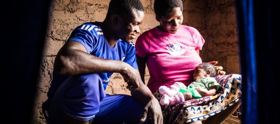 24 Mai 2018 - région de Kara, Togo. Tchassim Malidilé, 22 ans, regarde son bébé dans les bras de sa femme, Clarisse.